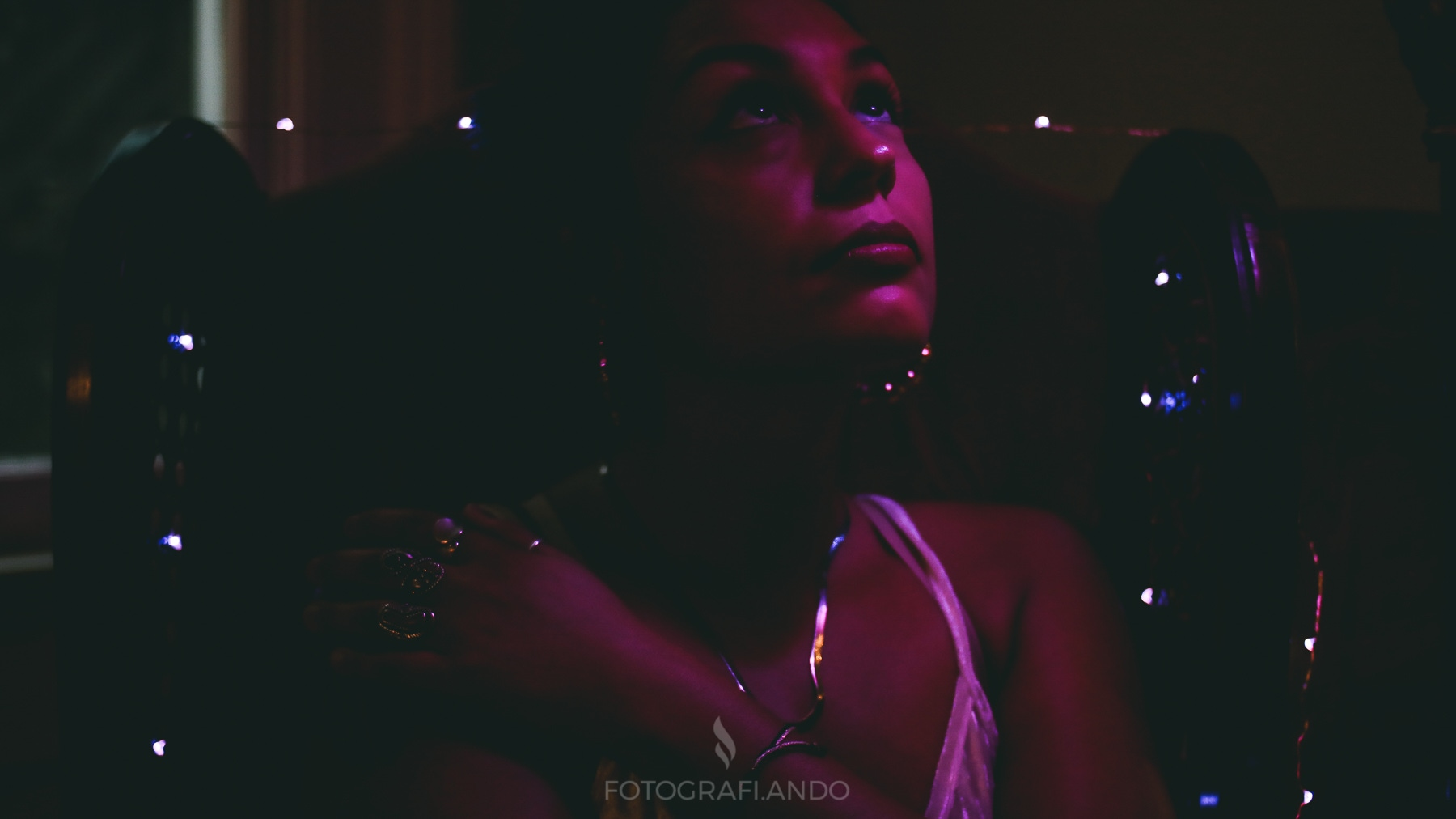 A woman of color in magenta lighting indoors, wreathed with tiny points of light, turns her face up to gaze upwards. She's wearing silver or gold jewelry and a strappy top.